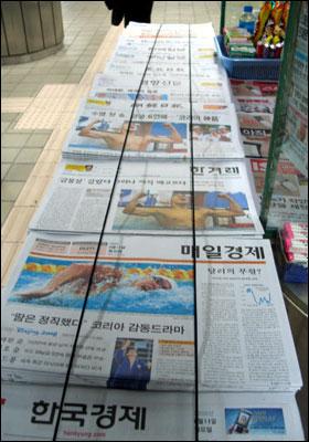 가판대 앞에 신문들이 가지런히 정렬되어 있다. 온통 1면은 박태환 선수의 금메달 소식이다.