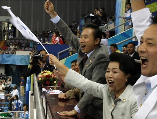 8월 9일 베이징 올림픽 여자 핸드볼 한국과 러시아의 경기에서 응원하는 이명박 대통령 내외. 이 대통령이 들고 응원한 태극기가 태극무늬 상하가 뒤바뀐 '거꾸로 태극기'로 밝혀져 논란이 됐다.