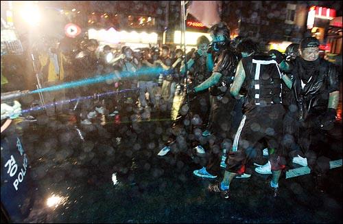 15일 저녁 서울 한국은행앞에서 '한미 쇠고기 재협상' '이명박 퇴진' 등의 구호를 외치며 제100차 촛불집회에 참석하는 시민들을을 향해, 경찰이 파란 색소를 섞은 물대포를 쏘며 강제해산 및 검거 작전에 나서고 있다.