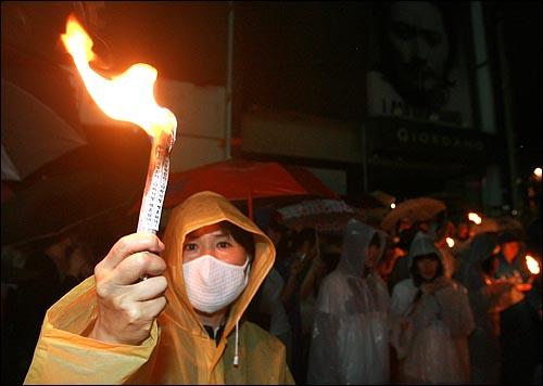 15일 개최된 '제100회 촛불문화제'에 참석한 시민들이 무차별 강제연행에 나선 경찰에 ?겨다니다 자정무렵 탑골공원앞 네거리에 모여 신문지를 말아서 불을 붙여 들고 있다.