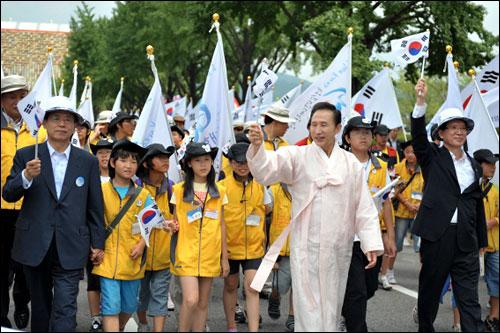 지난 15일 경복궁 앞 광장에서 열린 대한민국 건국60년 중앙경축식에 참석한 이명박 대통령이 청소년들과 함께 태극기를 앞세우고 시청 앞까지 행진하고 있다.