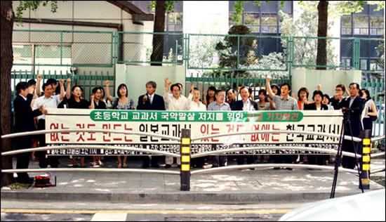 """항의 기자회견 국악교육 단체들이 교육과학기술부가 들어 있는 세종로 정부종합청사 뒤에서 항의 기자회견을 하고 있다. 펼침막엔 """"없는 것도 만드는 일본 교과서, 있는 것도 없애는 한국교과서""""라고 쓰여 있다."""