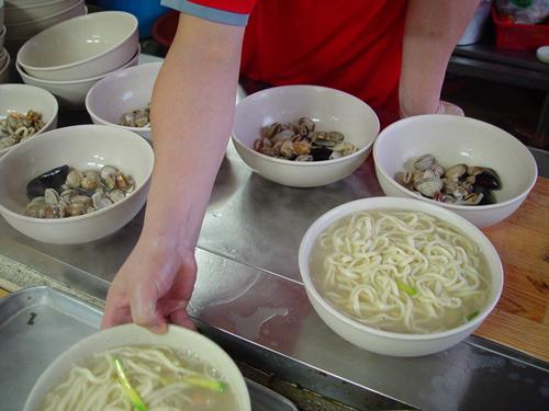 맛나게 만들어지고 있는 해물칼국수  바지락, 홍합등의 해물은 밑에 깔고 위에 호박과 김, 고추를 얹는다.