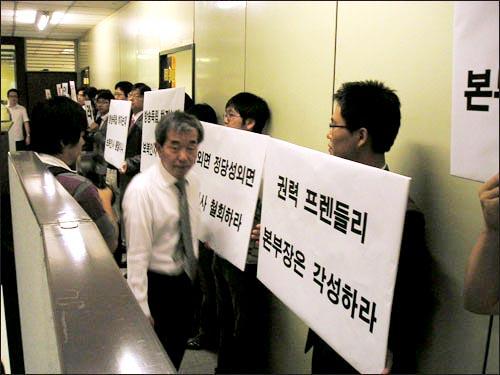 22일 오전 8시 KBS 기자협회 소속 기자들이 보도본부에서 지난 17일 인사발령에 항의하는 피켓시위를 벌이고 있다. 피켓시위를 하고 있는 기자들 앞으로 김종률 KBS 보도본부장이 지나가고 있다.