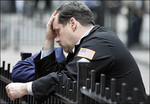 뉴욕증시가 미 하원이 금융위기 타개를 위한 7천억달러의 구제금융을 투입하는 법안을 부결시킨데 따른 충격파로 다우존스 산업평균지수는 지난주 종가보다 777.68포인트(6.98%) 빠진 10365.45에 거래를 마쳐, 사상 최대의 하락폭을 기록한 가운데 29일(현지시간) 뉴욕증권거래소 앞에서 한 딜러가 머리를 감싸고 쉬고 있다.