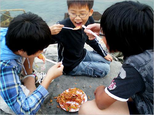 재첩비빔밥 어린이 3명이 바닷가 제방에서 재첩비빔밥을 맛있게 먹으면서 맵다고 야단법석이다.