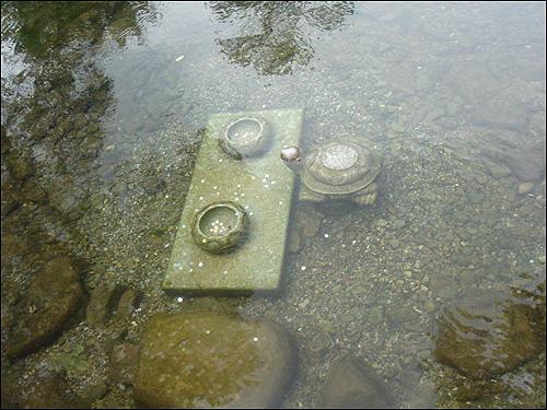 황지 돌다리 옆에는 목만 살짝 내민 거북이 한 마리와 동전이 여기저기 떨어져 있는 사각 진 돌 받침대 위에 동그란 그릇 두 개가 물에 잠겨 있다
