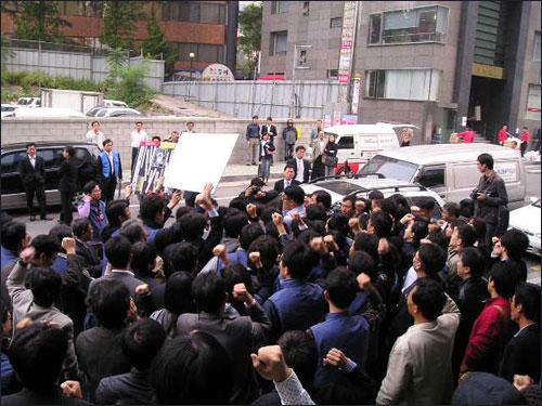 """15일 오전 구본홍 YTN 사장이 회사 출근을 시도했다가 조합원들에 가로막혀 돌아갔다. 조합원들이 """"위선자 물러가라"""" 등의 구호를 외치고 있다."""
