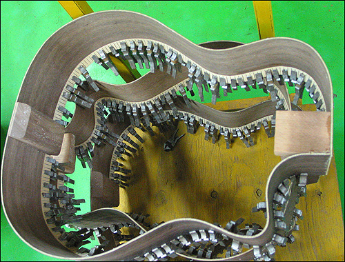기타 속에 이런 비밀이… 기타 안을 단단히 보듬어 주는 부분을 꽉 붙이기 위해 저렇게 일일이 두꺼운 핀셋으로 고정시켜 놓았다. 저 작업만해도 얼마나 많은 손길이 필요한 것인지….