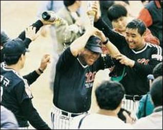 1990년, 트윈스의 첫 우승 우승 확정 순간 백인천 감독(가운데)에게 샴페인을 퍼붓고 있는 이병훈(오른쪽)
