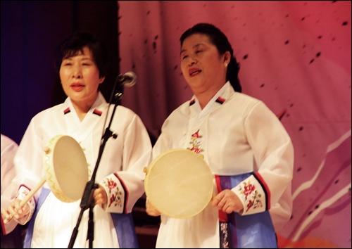 소고를 손에 들고 춤추며 민요를 부르는 친구부인(정면 오른쪽)