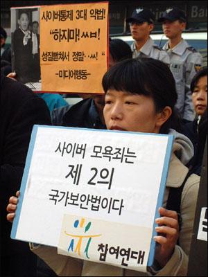 참여연대 활동가가 피켓을 들고 있다.