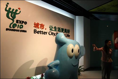 상하이엑스포 사무국 건물의 전시실에서 안내원이 설명하고 있다. 왼쪽은 상하이엑스포 마스코트인 '하이바오(海寶)'.