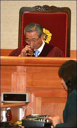 이강국 헌법재판소장이 13일 오후 서울 재동 헌법재판소 대심판정에서 종부세에 대한 헌법소원ㆍ위헌법률심판 사건에 대한 선고를 앞두고 물을 마시고 있다.
