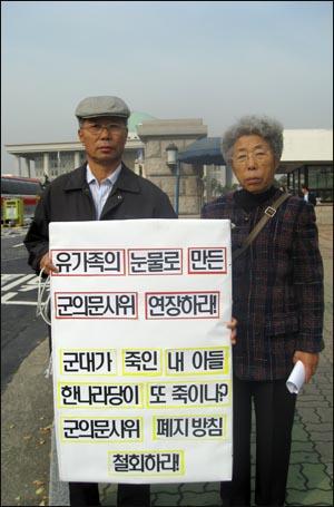 군의문사 유가족들이 14일 서울 여의도 국회의사당 앞에서 피켓시위를 벌이고 있다.