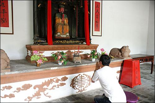 음식을 주관한 신 자오왕(?王)의 전각에서 예를 표하는 한 관광객. 자오왕 전각은 쓰촨요리박물관 중앙에 위치해 있다.