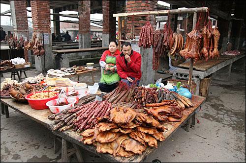 한 시골장터에서 훈제되거나 발효시킨 돼지고기를 파는 상인. 쓰촨은 중국에서 돼지고기 생산과 소비가 가장 많은 곳이다.