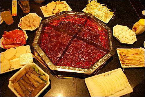 중국에서 가장 매운 음식으로 유명한 충칭(重慶)의 훠궈(火鍋). 고추와 산초로 만든 여러 소스에 생고추와 산초 알갱이를 통째로 넣었다.