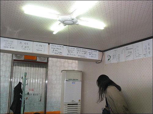 해장국 벽면 곳곳에 이 집 해장국 찬사와 함께 여러 사람들 사인이 빼곡하게 붙어 있다
