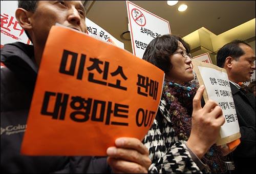 대형마트에서 미국산 쇠고기를 본격적으로 판매에 시작하는 27일 오후 서울 용산구 한강로 이마트용산점에서 광우병대책위 회원들이 미국산 쇠고기 판매를 항의하며 손피켓을 들어보이고 있다.