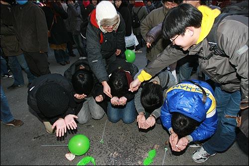 6일 저녁 서울 명동에서 민주민생국민회의 주최로 열린 '경제파탄 민주파괴 이명박 정권 심판 국민대회'에서 대학생들이 구걸하는 퍼포먼스를 벌이자 다른 참가자들이 동전을 던져주고 있다.
