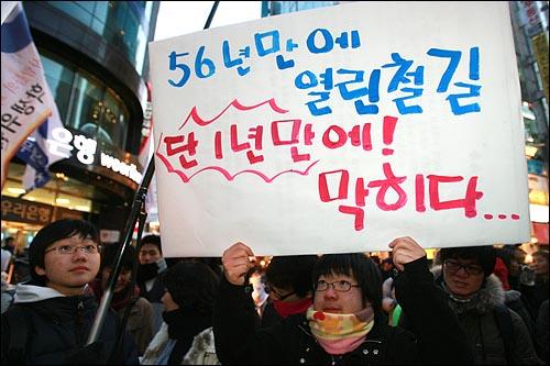 6일 저녁 서울 명동에서 민주민생국민회의 주최로 열린 '경제파탄 민주파괴 이명박 정권 심판 국민대회'에서 한 참가자가 경의선 남북열차 운행 중단을 안타까워하는 피켓을 들고 있다.