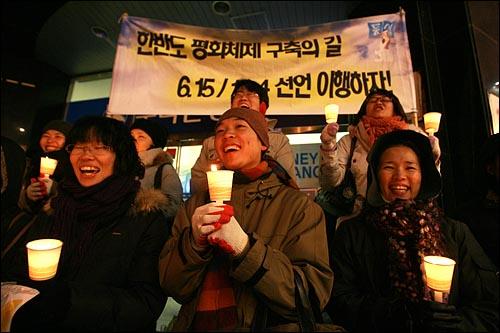 6일 저녁 서울 명동에서 민주민생국민회의 주최로 열린 '경제파탄 민주파괴 이명박 정권 심판 국민대회'에서 촛불을 든 참가자들이 지나가는 시민들을 향해 노래를 부르고 있다.