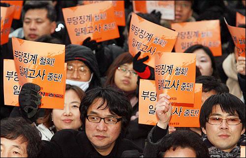 전교조 주최로 20일 오후 서울 광화문 열린마당에서 열린 전국교사대회에서 참석자들이 일제고사 거부 교사들에 대한 징계철회를 요구하며 구호를 외치고 있다.