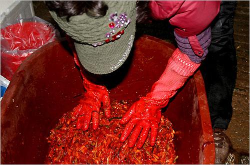 한 아주머니가 시장골목 어귀에서 홍어회무침을 버무리고 있다.
