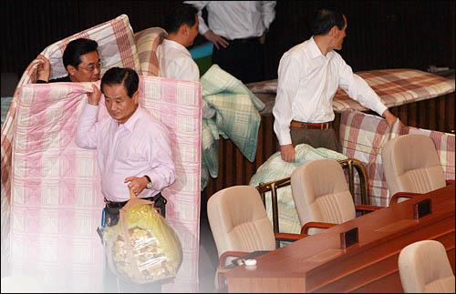 쟁점법안 처리를 둘러싼 여야 막판협상이 결렬된 30일 밤 국회의장의 질서유지권이 발동된 가운데 본회의장을 점거중인 민주당 의원들이 잠자리를 준비하고 있다.