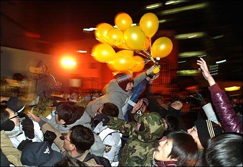 31일 밤 서울 종로 보신각 부근 평화박물관앞에서 전교조가 준비한 노란풍선을 경찰이 가로채려하자 한 시민이 경찰들을 저지선을 넘기 위해 몸을 날리고 있다.