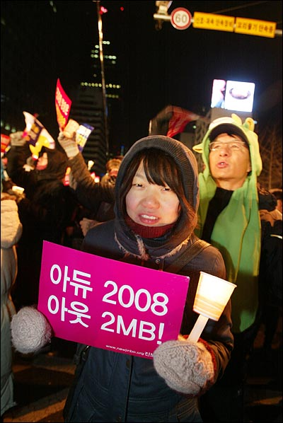 31일 밤 새해 보신각 타종식이 열리는 서울 종각 네거리에 모인 시민들이 '아듀 2008 아듀 MB!'가 적힌 종이 피켓을 들고 있다.