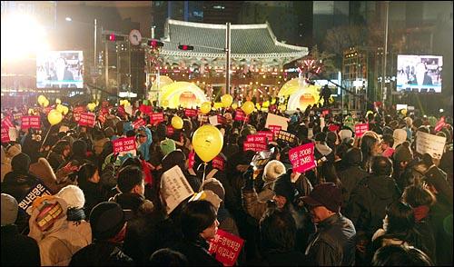 31일 밤 새해 보신각 타종식이 열리는 서울 종각 네거리에 모인 시민들이 '이명박 퇴진' '아듀 2008 아듀 MB!' '언론관계법 개악 철회하라' 등의 구호가 적힌 종이피켓과 '선생님을 돌려주세요'가 적힌 노란풍선을 들고 있다.