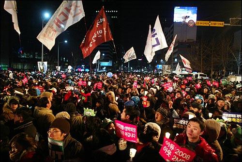 1일 새벽 서울 종로 보신각에서 2009년 새해를 알리는 타종식이 열리는 가운데, 이명박 정권을 규탄하는 피켓과 촛불을 든 시민들이 '이명박 퇴진'을 외치고 있다.