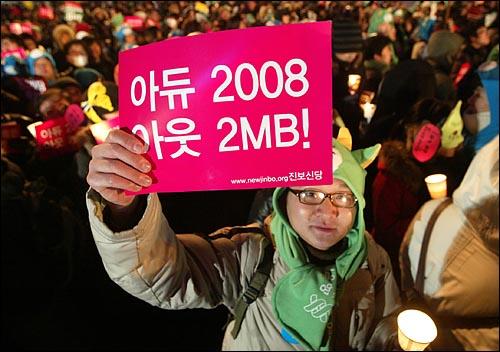 1일 새벽 서울 종로 보신각에서 2009년 새해를 알리는 타종식이 열리는 가운데, 촛불을 든 한 시민이 '아듀 2008, 아웃 2MB!'가 적힌 종이피켓을 들고 있다.