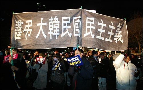 1일 새벽 서울 종로 보신각에서 2009년 새해를 알리는 타종식이 열리는 가운데, 보신각 주변에 모여 있는 시민들이 한나라당의 'MB악법' 강행처리 시도를 규탄하며 '근조 대한민국 민주주의'가 적힌 현수막을 들고 있다.