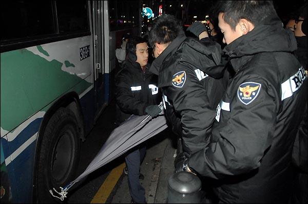 경찰이 31일 밤 종로 보신각 인근에서 깃발들 들고 서있는 한 인터넷 카페회원들의 깃발을 강제로 빼앗은채 황급히 자리를 피하고 있다.