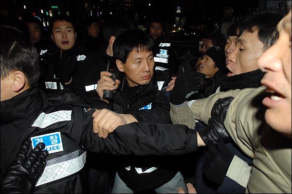 경찰이 31일 밤 종로 보신각 인근에서 깃발들 들고 서있는 한 인터넷 카페회원들의 깃발을 강제로 빼앗자 시민들이 깃발을 돌려달라며 강력히 항의하고 있다.