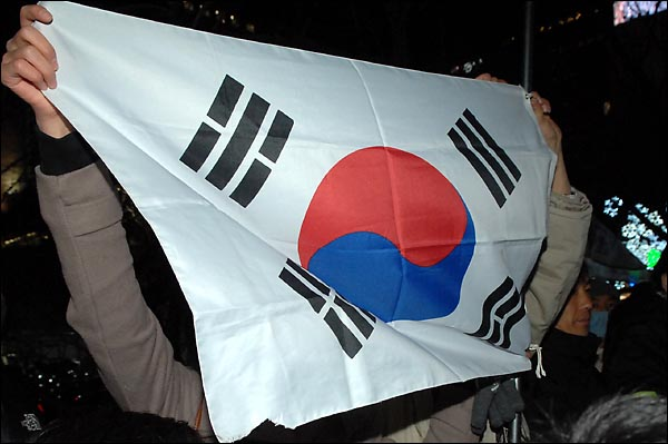 31일 밤. 경찰이 종로 보신각 인근에서 깃발들 들고 서있는 한 인터넷 카페회원들에게 깃발을 내릴것을 요구하자 한 시민들이 이에 항의하며 태극기를 펼쳐 보이고 있다.