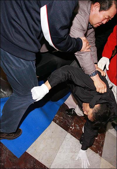 국회사무처가 국회 본회의장 입구에서 농성중인 민주당 당직자들과 보좌진에 대해 3일 오후 강제해산에 나서 농성단을 끌어내려는 국회 경위, 방호원들과 이를 저지하려는 당직자, 보좌진이 한데 뒤엉켜 격한 몸싸움을 벌이고 있다. 박주선 의원이 당직자를 끌어내려는 경위를 제압하고 있다.