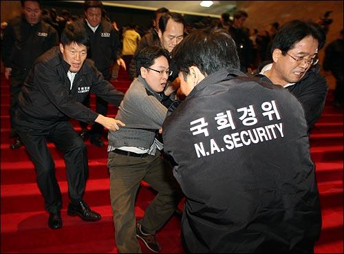 국회 사무처가 경위를 투입하여 국회 로텐더홀에서 농성중인 민주당의원과 당직자들을 강제해산시도에 나선 가운데 3일 밤 서울 여의도 국회에서 국회 경위들이 민주당 당직자를 끌어내고 있다.