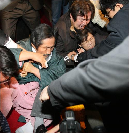 지난 1월 국회 본회의장 앞에서 쟁점법안 일방처리에 반대해 연좌 농성을 벌이던 민주노동당 강기갑, 이정희 의원이 본회의장 입구에 재설치하려던 현수막을 철거하려는 국회 경위들에 맞서 사투를 벌이고 있다.