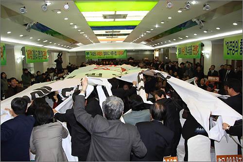 참석자들이 '재벌 방송, '재벌 은행', '휴대폰 도청' 등 'MB악법'이라고 쓰인 대형천을 찢는 퍼포먼스를 펼치고 있다.