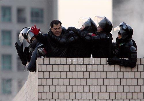20일 새벽 서울 용산구 신용산역 부근 재개발 지역내 5층 건물 옥상에서 철거민들이 농성을 벌이는 가운데 경찰특공대가 철거민들을 제압하고 있다.