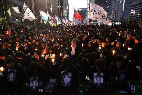 서울 청계광장에서 열릴 예정이었던 '용산 철거민 살인진압 희생자 제2차 범국민추모대회'가 경찰의 원천봉쇄로 인해 31일 저녁 청계광장 부근 한국관광공사앞으로 장소를 옮겨 개최된 가운데, 희생자의 영정사진을 든 한 유가족들과 시민들이 촛불을 들고 추모집회를 열고 있다.