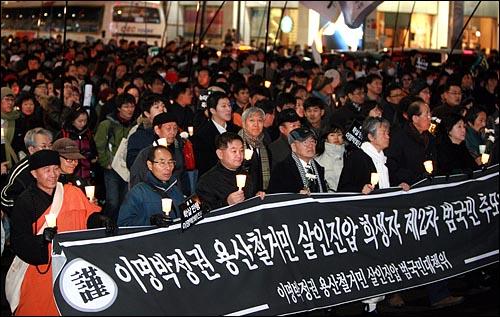 '용산 철거민 살인진압 희생자 제2차 범국민추모대회'에 참석했던 시민 수천명이 31일 밤 서울 명동 입구에서 행진을 벌이고 있다.