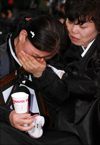 1일 서울 청계광장에서 열린 '폭력살인진압 규탄 및 MB악법 저지를 위한 국민대회' 참석한 철거민 희생자 유족들이 영정사진을 들고 오열하고 있다.