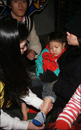 1일 저녁 서울 을지로 입구 '폭력살인진압 규탄 및 MB악법 저지를 위한 국민대회' 참가자들과 경찰과의 충돌 과정에서 경찰 방패에 정강이를 맞은 한 어린이가 의료지원팀의 진료를 받고 있다.