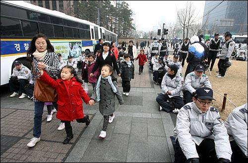 7일 오후 '용산철거민참사 희생자 제3차 추모범국민대회'가 열릴 예정인 서울 청계광장 주변을 경찰병력이 겹겹이 에워싸서 원천봉쇄하고 있는 가운데 어린이들이 경찰들 곁을 지나고 있다.