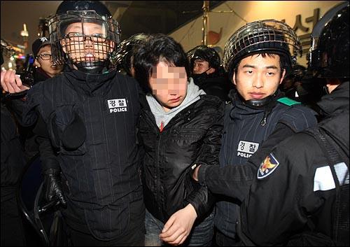 한 대학생이 6일 저녁 서울 중구 퇴계로 4가 앞에서 옷에 색소 분사기를 맞은 흔적이 있자 경찰들에게 강제연행 되고 있다.